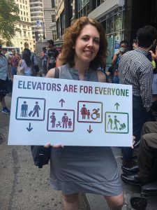 "Photo of Jessica Murray holding a sign in front of a rally. The sign reads, ""Elevators are for everyone"" and shows iconic drawings of people in different elevators. The first shows a person with crutches and a person rolling a suitcase. The second has a pregnant woman, a baby in a stroller, a person with a heart condition, and a child. The third shows a woman with a child and a person in a wheelchair. The last one shows a person with a cane, and a person rolling a dolly with packages. The graphic and text has a rainbow gradient, symbolizing inclusiveness. The mposter was designed by Jessica Murray for a rally outside of an MTA board meeting in July, 2017. She hopes they will consider the diverse cross-section of the population that needs elevators."